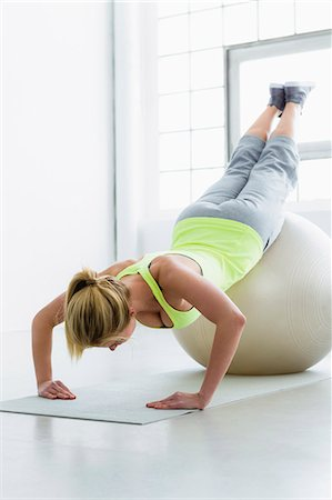 Young woman doing press up with exercise ball Stock Photo - Premium Royalty-Free, Code: 649-07585507