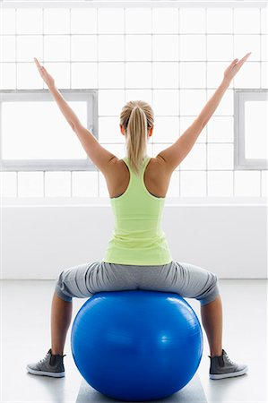 Young woman sitting on exercise ball, arms raised, rear view Stock Photo - Premium Royalty-Free, Code: 649-07585501