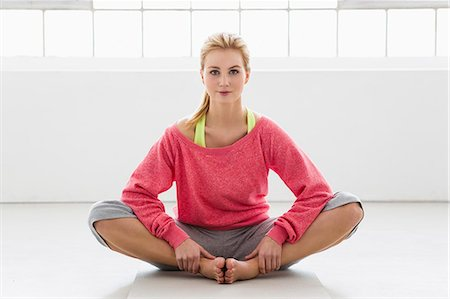 stretch - Young woman sitting on exercise mat Stock Photo - Premium Royalty-Free, Code: 649-07585510