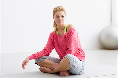 Young woman sitting on exercise mat Stock Photo - Premium Royalty-Free, Code: 649-07585511
