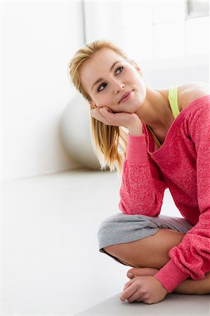 Young woman sitting on exercise mat Stock Photo - Premium Royalty-Free, Code: 649-07585512