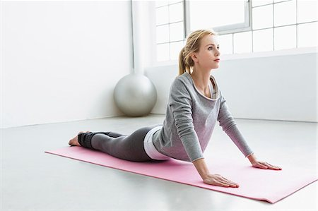 Young woman in yoga pose on yoga mat Stock Photo - Premium Royalty-Free, Code: 649-07585525