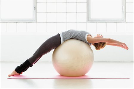 physical fitness - Young woman stretching on exercise ball Stock Photo - Premium Royalty-Free, Code: 649-07585529