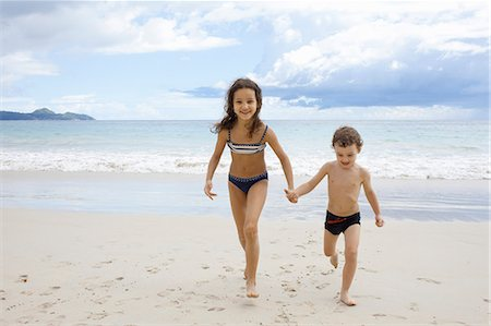 Brother and sister running on beach, holding hands Stock Photo - Premium Royalty-Free, Code: 649-07585549