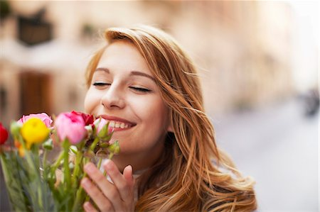 smelling - Smiling young woman smelling a bunch of flowers Stock Photo - Premium Royalty-Free, Code: 649-07585577