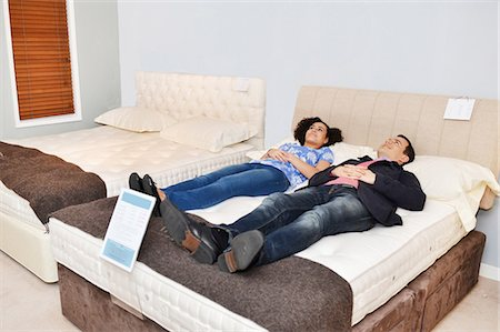 Couple lying on bed in furniture shop showroom Stock Photo - Premium Royalty-Free, Code: 649-07585584