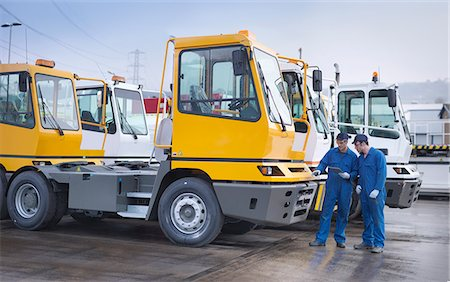 Engineers inspecting parked trucks at truck repair factory Stock Photo - Premium Royalty-Free, Code: 649-07585619