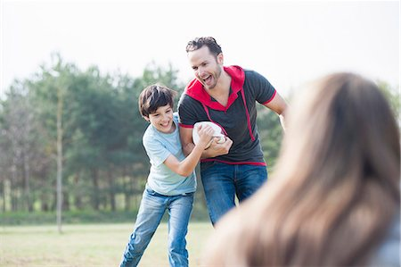 Father and son practicing rugby tackle in park Stock Photo - Premium Royalty-Free, Code: 649-07585714