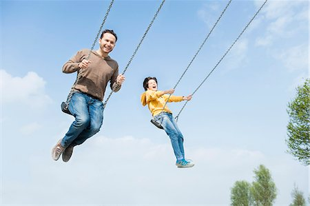 swing (sports) - Father and son having fun on park swings Stock Photo - Premium Royalty-Free, Code: 649-07585724
