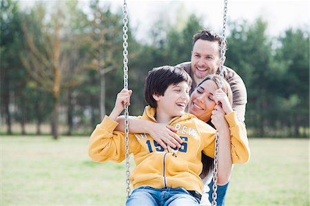 preteen boys playing - Parents hugging son on park swing Stock Photo - Premium Royalty-Free, Code: 649-07585722