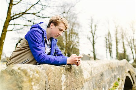 Unhappy teenage boy leaning over rural bridge Stock Photo - Premium Royalty-Free, Code: 649-07585747