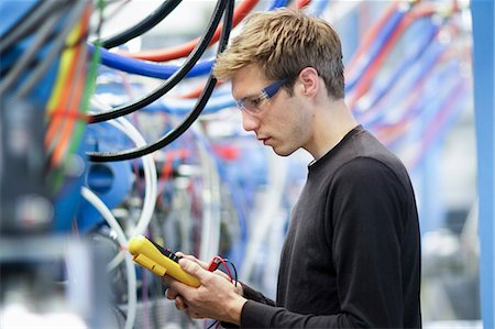 Mid adult male technician testing cables in engineering plant Stock Photo - Premium Royalty-Free, Code: 649-07585770