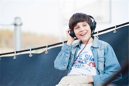 Boy wearing headphones in hammock Stock Photo - Premium Royalty-Free, Code: 649-07585800
