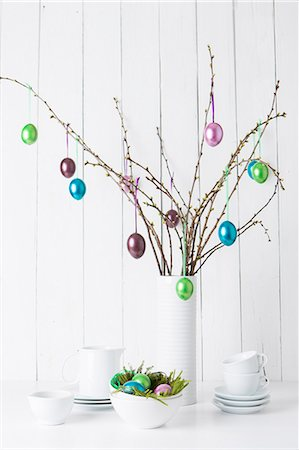 Still life of crockery and shiny easter eggs hanging from twigs Stock Photo - Premium Royalty-Free, Code: 649-07596074
