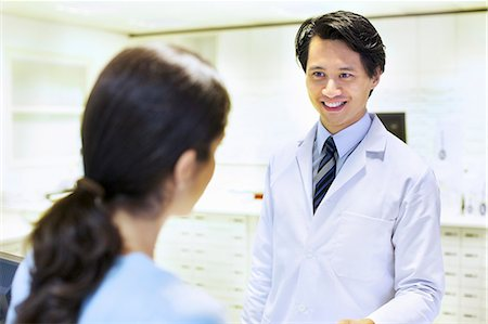 Male pharmacist handing prescription to customer Stock Photo - Premium Royalty-Free, Code: 649-07596143