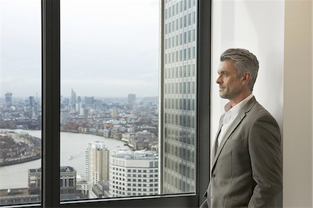 Portrait of mature businessman looking out of office window, Canary Wharf, London, UK Stock Photo - Premium Royalty-Free, Code: 649-07596239