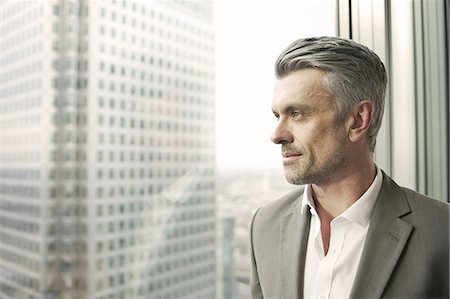 Portrait of mature businessman looking out of office window Stock Photo - Premium Royalty-Free, Code: 649-07596240