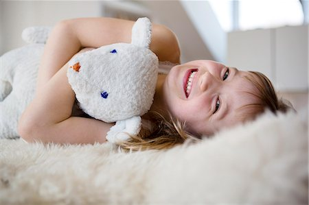 Girl lying on furry bed cuddling teddy bear Stock Photo - Premium Royalty-Free, Code: 649-07596257