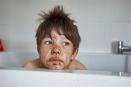 Boy with muddy face, sitting in bath Stock Photo - Premium Royalty-Free, Code: 649-07596305
