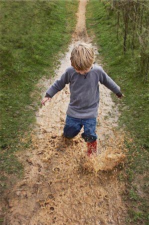 dirty - Boy splashing through muddy puddle Stock Photo - Premium Royalty-Free, Code: 649-07596306