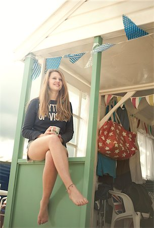Teenage girl sitting on beach hut porch, Southwold, Sussex, UK Stock Photo - Premium Royalty-Free, Code: 649-07596378
