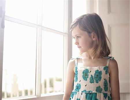 Portrait of a girl looking out of bedroom window Stock Photo - Premium Royalty-Free, Code: 649-07596396