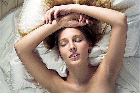 Young woman lying on bed with eyes closed Stock Photo - Premium Royalty-Free, Code: 649-07596424