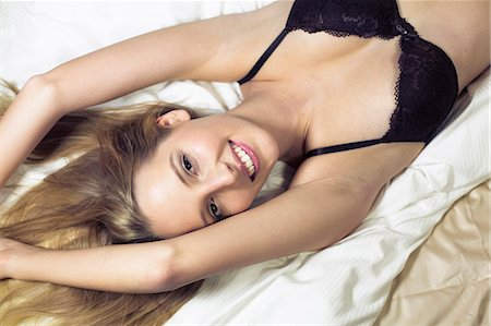 Young woman lying on bed wearing bra Stock Photo - Premium Royalty-Free, Code: 649-07596422