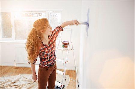 Teenage girl painting her bedroom wall Stock Photo - Premium Royalty-Free, Code: 649-07596482