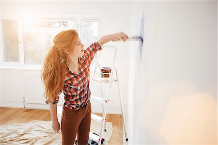 Teenage girl painting her bedroom wall Stock Photo - Premium Royalty-Free, Code: 649-07596482