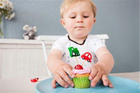 Baby boy playing with cupcake Stock Photo - Premium Royalty-Free, Code: 649-07596604