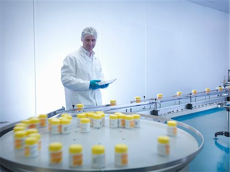 Worker inspecting packaging in pharmaceutical factory Stock Photo - Premium Royalty-Free, Code: 649-07596687
