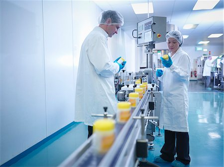 Workers inspecting packaging in pharmaceutical factory Stock Photo - Premium Royalty-Free, Code: 649-07596688