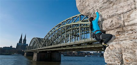 Female climber on man made wall next to the Hohenzollern railway bridge, Cologne, Germany Stock Photo - Premium Royalty-Free, Code: 649-07596682