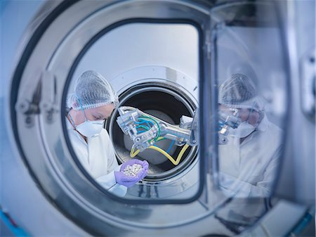 Worker inspects tablets in coating machine in pharmaceutical factory Stock Photo - Premium Royalty-Free, Code: 649-07596698