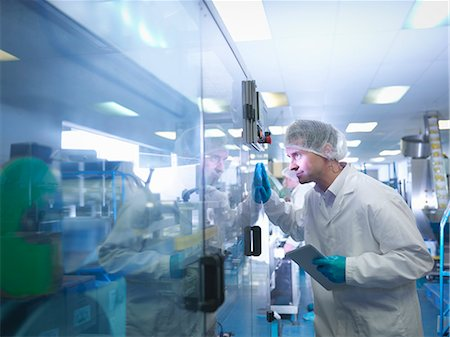 science & technology - Worker inspecting tablets as they are put into packaging in pharmaceutical factory Stock Photo - Premium Royalty-Free, Code: 649-07596692