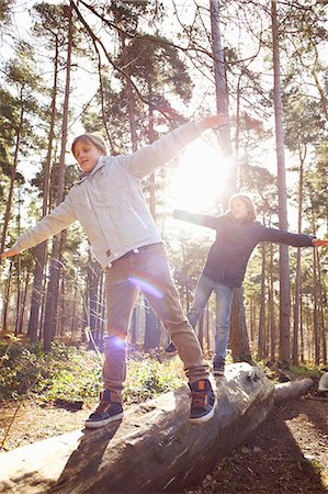 family  fun  outside - Twin brothers walking along fallen tree trunk in forest Stock Photo - Premium Royalty-Free, Code: 649-07596716