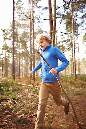 preteen boys playing - Boy running with a stick in woods Stock Photo - Premium Royalty-Free, Code: 649-07596725