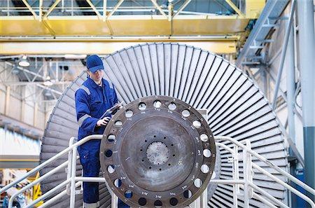Engineer inspecting turbine in workshop Stock Photo - Premium Royalty-Free, Code: 649-07596738
