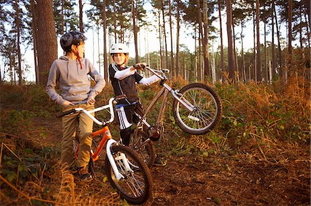 Twin brothers holding BMX bikes chatting in forest Stock Photo - Premium Royalty-Free, Code: 649-07596733