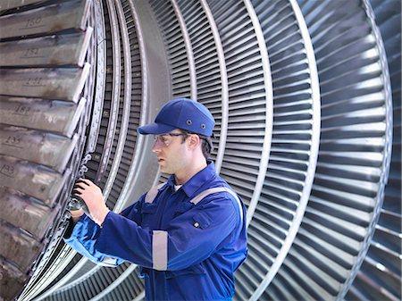 people working in factory - Engineer inspecting repair to steam turbine blade in workshop Stock Photo - Premium Royalty-Free, Code: 649-07596746