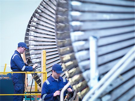 Engineers repairing steam turbine in repair bay in workshop Stock Photo - Premium Royalty-Free, Code: 649-07596755