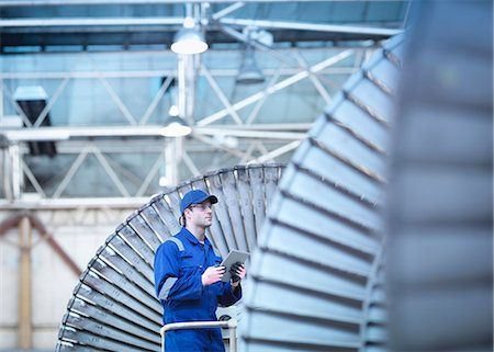 Engineer inspecting steam turbine in repair bay Stock Photo - Premium Royalty-Free, Code: 649-07596756