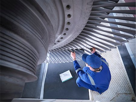 Engineer inspecting steam turbine in repair works Stock Photo - Premium Royalty-Free, Code: 649-07596758