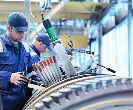 Engineers fitting blades to steam turbine in turbine repair works Stock Photo - Premium Royalty-Free, Code: 649-07596761