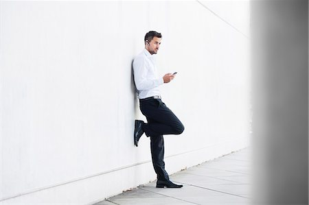 Young businessman leaning against wall texting on smartphone Stock Photo - Premium Royalty-Free, Code: 649-07647755