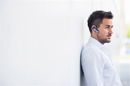 Young businessman leaning against wall listening to bluetooth set Stock Photo - Premium Royalty-Free, Code: 649-07647752