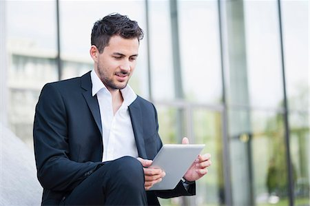 Young businessman outside office with digital tablet Stock Photo - Premium Royalty-Free, Code: 649-07647761