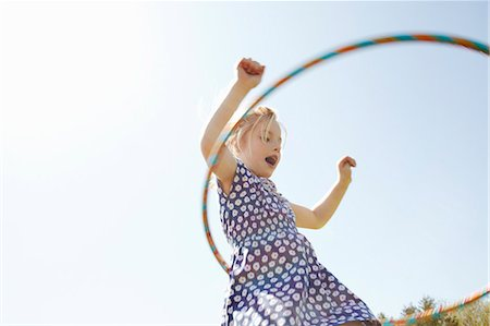 playing - Low angle view of girl playing with plastic hoop Stock Photo - Premium Royalty-Free, Code: 649-07647801