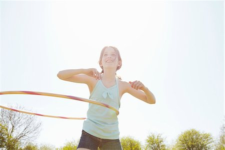 Girl playing with plastic hoop Stock Photo - Premium Royalty-Free, Code: 649-07647802